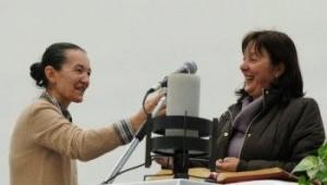 Ivanka recebe o microfone da colega vidente Vicka Ivankovic-Mijatovic quando Ivanka parceria com Vicka para uma aparição surpresa em Corridonia, Itália,