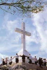 """Grupo de peregrinos rezando sob a cruz no topo da Montanha da Cruz. De acordo com uma mensagem no início,  a Virgem Maria também vai lá : """"Eu estou muitas vezes na Montanha da Cruz, aos pés da Cruz, rezando lá"""", ela disse em 3 de novembro de 1981."""