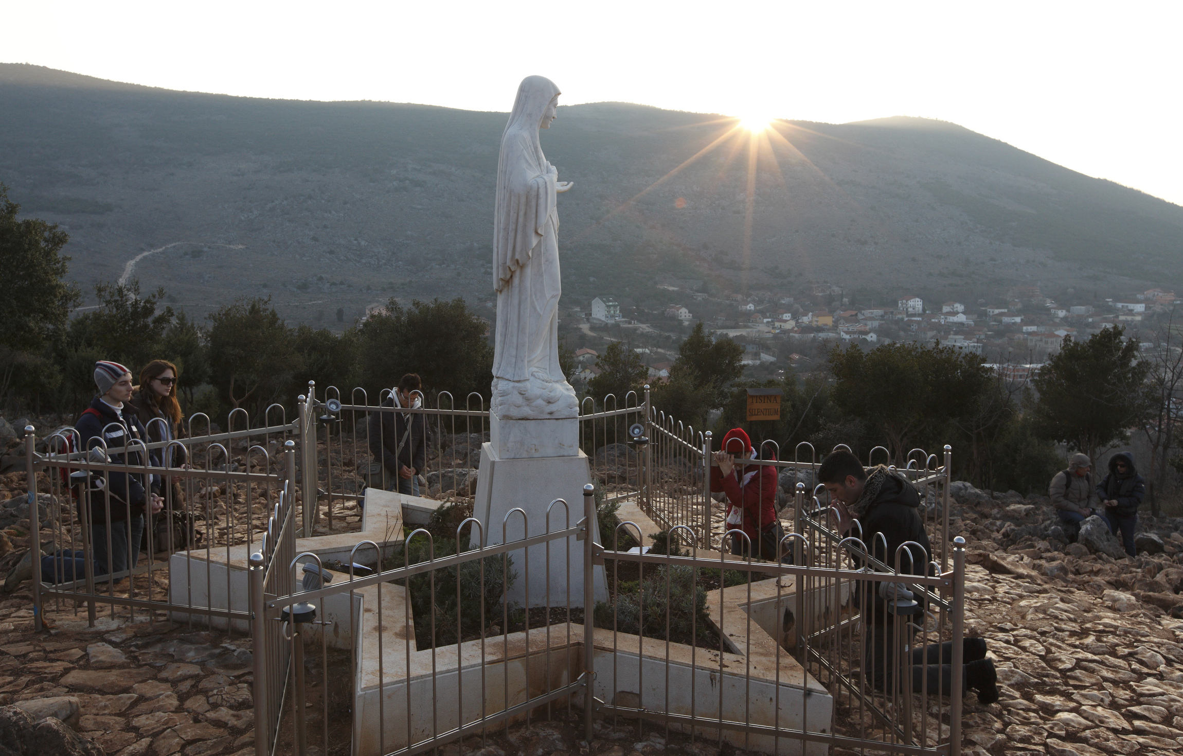 PILGRIMS PRAY AROUND STATUE OF MARY ON APPARITION HILL IN MEDJUGORJE